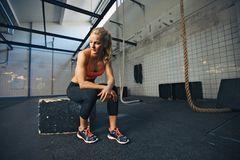 Fit young woman taking break after workout at gym. Caucasian female athlete sitting on a box at gym thinking. Fit young woman taking break after her workout at stock image