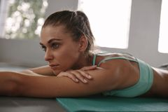 Fit young woman taking rest after workout. Close up of fit young woman taking rest after workout in health club. Female lying on exercise mat in gym and looking Royalty Free Stock Photo