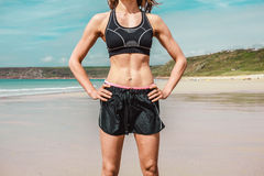 Fit young woman with toned abs on beach Stock Images