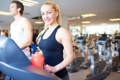 Fit Young Woman on Treadmill Smiling at Camera Stock Photography