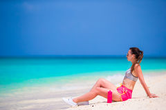 Fit young woman on tropical white beach in her sportswear Stock Images