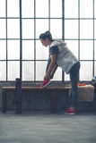 Fit young woman tying shoe on bench by window in city loft gym Royalty Free Stock Photo