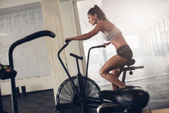 Fit young woman using exercise bike at the gym. Fitness female using air bike for cardio workout at crossfit gym Royalty Free Stock Images