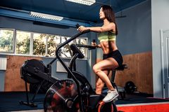 Fitness female using air bike for cardio workout at crossfit gym. Royalty Free Stock Photos