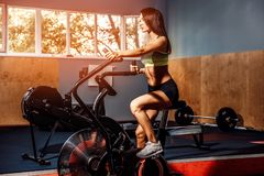 Fitness female using air bike for cardio workout at crossfit gym. Royalty Free Stock Photo