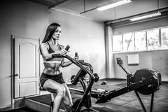 Fitness female using air bike for cardio workout at crossfit gym. Royalty Free Stock Photography
