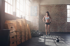 Fit young woman walking in the crossfit gym. Full length image of fit young woman walking in the crossfit gym. Female athlete preparing herself before a intense stock images