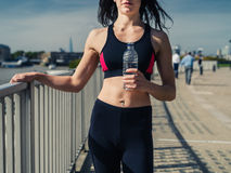 Fit young woman with water bottle in city. A fit and athletic young woman is resting after a workout and is standing in the city with a water bottle in her hand Stock Photography