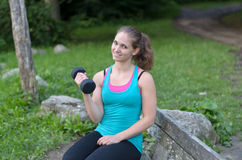 Fit young woman working out with a dumbbell Stock Images
