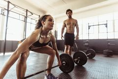 Female athlete lifting weights at cross training gym. Fit young women exercising with barbell and men standing in background. Female athlete lifting heavy Royalty Free Stock Image