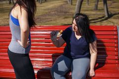 Fit young woman motivate her friend to stop eating junk food. He. Fit young women motivate her friend to stop eating junk food. Health care, weight loss stock image