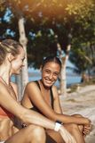 Smiling young female friends sitting together outside before a r royalty free stock photography