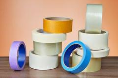 A fita adesiva na variedade encontra-se na tabela no fundo alaranjado Imagens de Stock