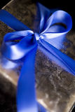 Fita azul amarrada em uma curva no presente de prata. Foto de Stock