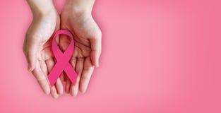 Fita cor-de-rosa nas mãos para a conscientização do câncer da mama