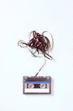 A fita da cassete áudio com subtraído para fora grava sobre a placa de madeira textured azul Fotografia de Stock