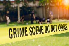 Fita da cena do crime e fundo borrado da equipe da aplicação da lei fotografia de stock