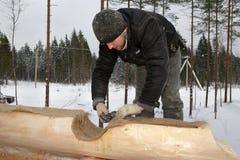 A fita da isolação térmica dos lugares do carpinteiro nos logs surge Fotos de Stock