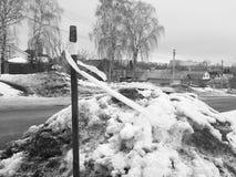 Fita da parada da constru??o em uma vara no fundo da neve e das estradas em um monte de neve no inverno ou na mola fotografia de stock