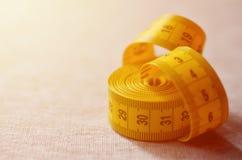 A fita de medição amarela com os indicadores numéricos sob a forma dos centímetros ou das polegadas encontra-se em uma tela feita Imagem de Stock