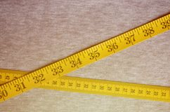 A fita de medição amarela com os indicadores numéricos sob a forma dos centímetros ou das polegadas encontra-se em uma tela feita Imagens de Stock Royalty Free