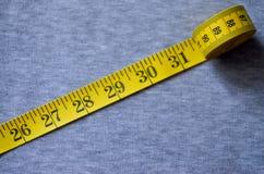 A fita de medição amarela encontra-se em uma tela feita malha cinza Fotos de Stock