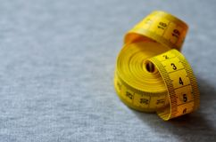 A fita de medição amarela encontra-se em uma tela feita malha cinza Foto de Stock Royalty Free