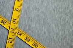A fita de medição amarela encontra-se em uma tela feita malha cinza Fotografia de Stock