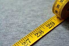 A fita de medição amarela encontra-se em uma tela feita malha cinza Imagem de Stock Royalty Free
