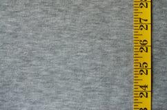 A fita de medição amarela encontra-se em uma tela feita malha cinza Fotos de Stock Royalty Free