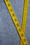 A fita de medição amarela encontra-se em uma tela feita malha cinza Imagens de Stock