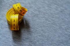 A fita de medição amarela encontra-se em uma tela feita malha cinza Fotografia de Stock Royalty Free