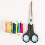 A fita de medição com carretel e scissor no branco Fotografia de Stock Royalty Free