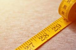 A fita de medição da cor amarela com os indicadores numéricos sob a forma dos centímetros ou das polegadas encontra-se em uma tel Foto de Stock Royalty Free