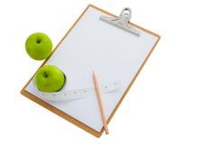 Fita de medição envolvida em torno de uma maçã e de uma prancheta verdes Imagem de Stock