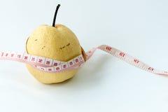 Fita de medição envolvida em torno de uma pera chinesa foto de stock