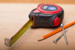 Fita de medição, lápis, parafusos na tabela de madeira fotografia de stock