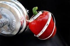 A fita de medição ondula acima em uma pimenta doce vermelha com peso de prata Foto de Stock