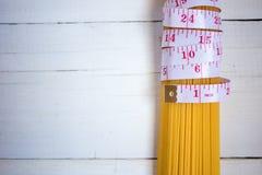 Fita de medição, tema da dieta com grupo dos espaguetes italianos crus da massa no fundo de madeira branco Dieta, alimento saudáv foto de stock