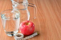 Fita de medição, vidro da maçã e de água para saudável e corpo magro Fotos de Stock Royalty Free
