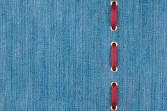 A fita de seda vermelha é introduzida em uma tela clara da sarja de Nimes com lugar para seu texto Fotos de Stock Royalty Free