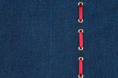 A fita de seda vermelha é introduzida em uma tela escura da sarja de Nimes com lugar para seu texto Imagem de Stock Royalty Free