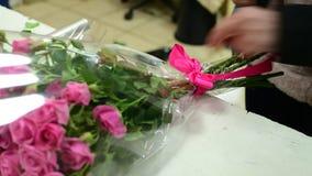 Fita do laço do florista em um ramalhete de rosas cor-de-rosa video estoque