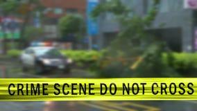 Fita do limite e carro-patrulha defocused na cena do crime filme