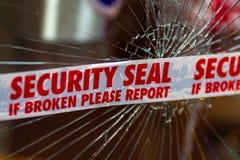 Fita do selo da segurança da polícia através de janela de vidro quebrada foto de stock royalty free