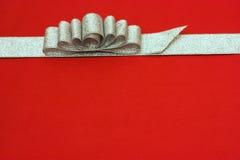 Fita e curva de prata do presente no fundo vermelho. alguns Fotos de Stock