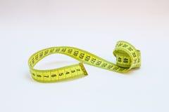 Fita métrica amarela nos medidores e polegadas em uma espiral Imagens de Stock Royalty Free