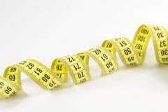 Fita métrica amarela nos medidores e polegadas em uma espiral Foto de Stock