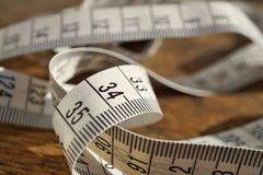 Fita métrica branca do comprimento de medição da fita nos medidores e nos centímetros no woodensurface como o símbolo da ferramen Imagem de Stock Royalty Free