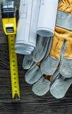 A fita métrica da construção das luvas protetoras planeia no varrão de madeira Imagem de Stock Royalty Free